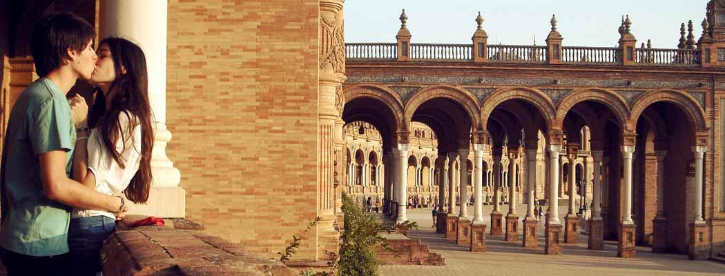 Una pareja, seguramente estudiantes de un máster MBA en Sevilla, besándose en la Plaza de España de Sevilla.