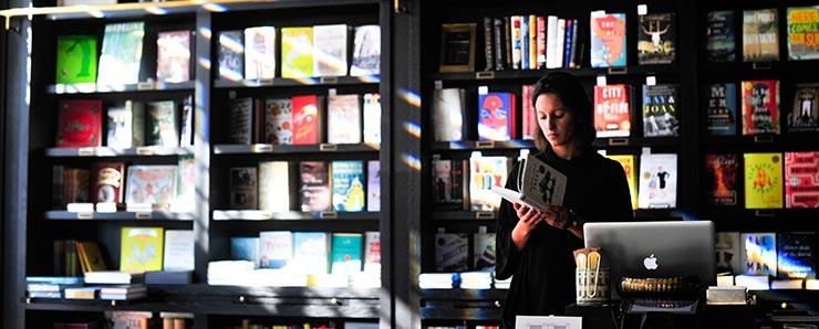 Mujer en una librería leyendo un libro sobre MBA.