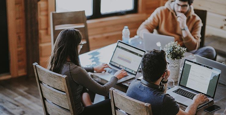 Grupo de personas estudiando un MBA online a distancia con sus ordenadores laptop.
