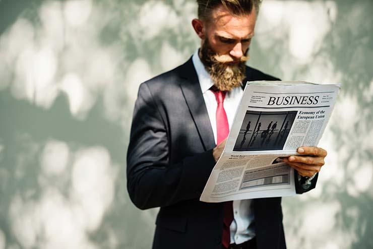 Un estudiante de un máster MBA presencial leyendo un periódico de negocios.