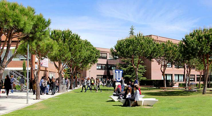 Exterior de la Universidad Francisco de Vitoria: un espacio con césped en el suelo lleno de estudiantes. Al fondo varios edificios. Lugar donde se estudia el MBA de la UFV.